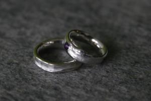 Organisch gevormde zilveren partnerringen met cabuchon geslepen amethyst die in de vorm opgaat.